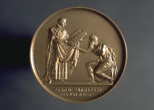 Revers d'une médaille du Grand Sanhédrin de 1806 : Napoléon debout revêtu de sa toge d'empereur donnant les Tables de la Loi à Moïse agenouillé devant lui© MAHJ